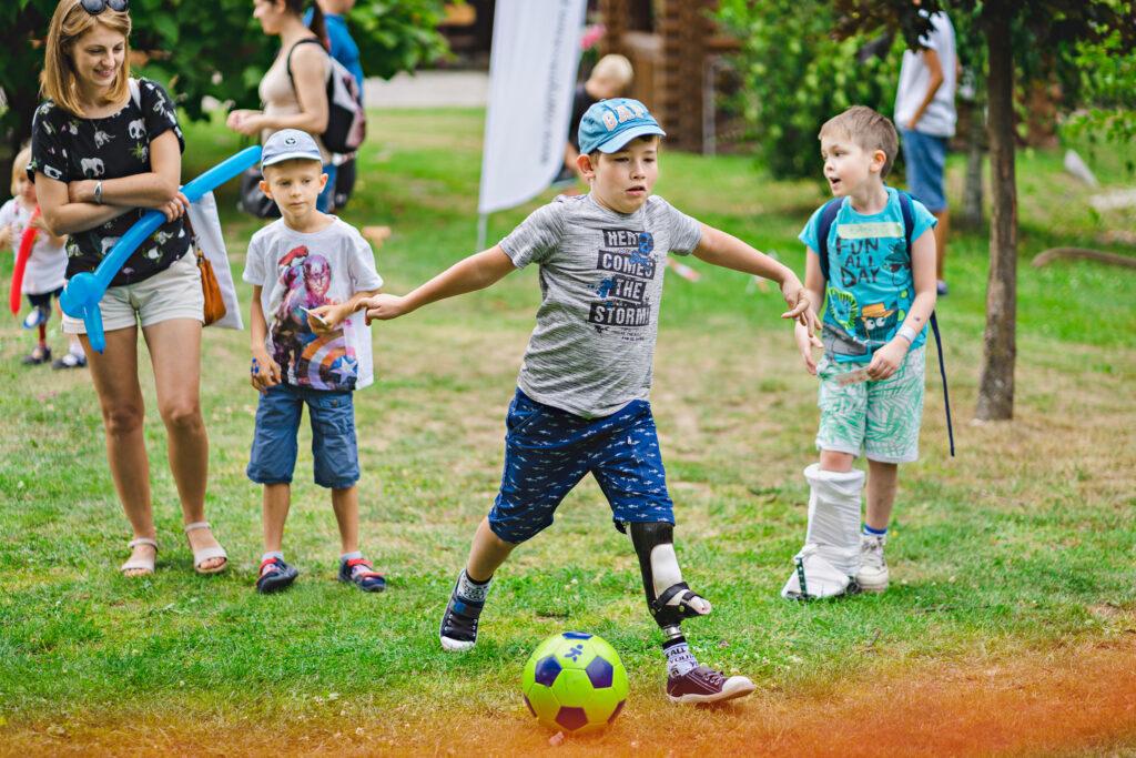 chłopiec z protezą grający w piłkę